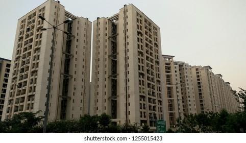 Low angle shot of a high rise newly constructed luxury apartments in New Delhi NCR, Mumbai, Kolkata, Gurgaon, Bangalore, Hyderabad, Pune, Noida, Raipur, Amaravati, India against sky