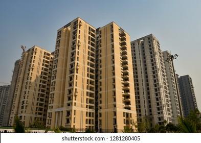 Low angle shot of a high rise multi storey newly constructed luxury residential apartments in New Delhi NCR, Mumbai, Kolkata, Gurgaon, Bangalore, Hyderabad, Pune, Noida, India against blue sky