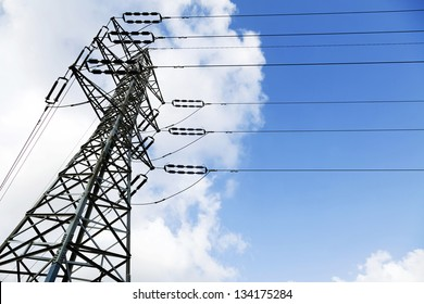 Low angle shot of a high-voltage electricity pylon and power lines, on the background of the blue & white cloudy sky.