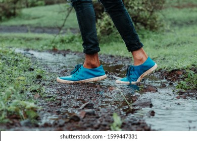 Low angle shot of the leg of person wearing blue shoes in the river stream in forest