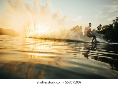 Low angle shot of man wakeboarding on a lake. Man water skiing at sunset.