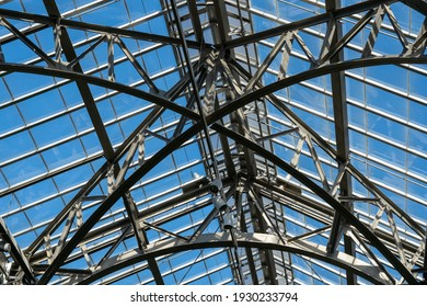 A low angle shot of metallic construction with a glass roof