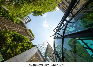 Low angle shot of modern glass buildings and green with clear sky background.