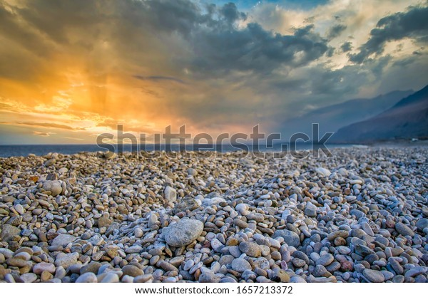 Low Angle shot of pebble beach bathed in orange light during sunset. From Sur, Muscat, Oman.