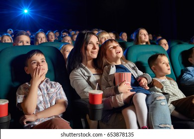 Low angle shot of people watching a movie at the cinema. Young woman and her daughter enjoying a film at the movie theatre motherhood parenting children kids entertaining happiness.