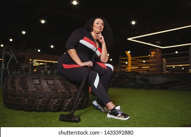 Low angle shot of a plus size woman in sportswear resting at the gym after exercising with sledgehammer. CHeerful overweight sportswoman relaxing after hitting heavy wheel with a hammer, copy space