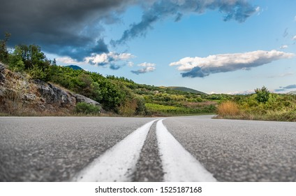 Low angle shot of road and green hills with blue sky and clouds.