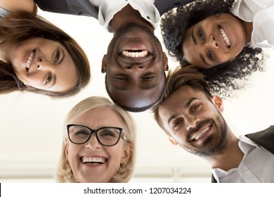 Low angle shot of smiling diverse office employee looking at camera hugging happy with career choice or company, excited multiethnic work team standing in circle engaged in team building activity