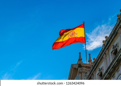 Low angle shot spain flag waving at top of building.