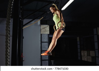 Low angle shot of a sportswoman doing ring dips at the fitness and crossfit gym. Gorgeous young woman performing crossfit and fitness workout complex using gymnastic rings at gym studio