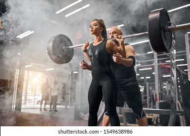 Low angle shot of sporty friends training in underground garage, standing in white smoke, holding heavy black barbell, brutal professional sportsman supporting young female partner, indoor shot