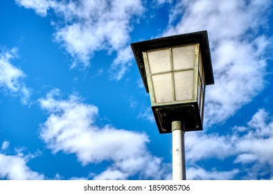 A low angle shot of a streetlamp against a cloudy blue sky