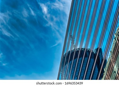 A low angle shot of a tall glass building under a blue cloudy sky
