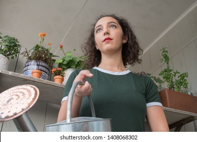 Low angle shot of a woman holding a grey tin watering can getting ready to feed her hungry plants resting in her garden on her outdoor porch with a blank expression on her face.