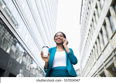Low angle shot of young elegant african american business woman in formal wear talking on phone and holding takeaway coffee cup while walking outside office during the break