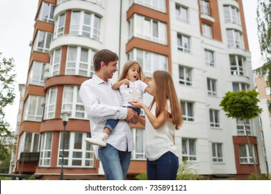 Low angle shot of a young happy family posing in front of new apartment building. Father and mother holding their cute little daughter.Excited family with a little kid posing with a key to a new house