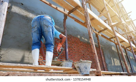 Low angle and side view of Asian builder man on wooden scaffolding is working to plaster cement on brick wall background in construction site, focus on foreground