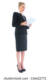 Low angle side view of attractive blonde businesswoman making use of her tablet on white background