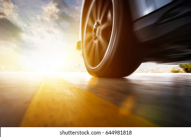 Low angle side view of car driving fast at sunset with motion speed effect .