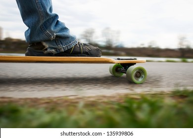 Low angle side view of a skater on a longboard skateboarding.
