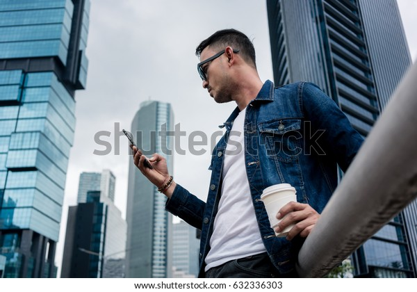 Low angle side view of a young man wearing denim jacket while using his smartphone outdoors in a business district with modern architecture