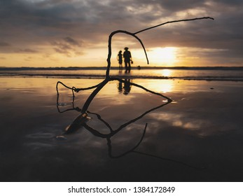 Low angle silhouette of Mom and daughter enjoying the golden sunset and having a quality time at Kuta beach, Bali, Indonesia