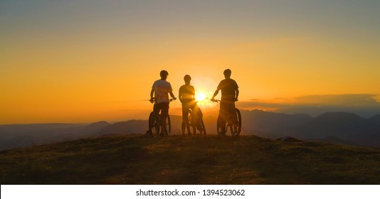 LOW ANGLE, SILHOUETTE, SUN FLARE: Golden evening sun rays illuminate cross country bikers on the mountaintop observing the scenic landscape. Three friends watch sunset after bicycle ride in mountains