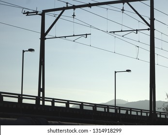 Low angle silhouette view of railway line poles with electric overhead wires, Lower Hutt New Zealand