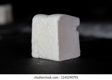 Low Angle of Single Marshmallow Cube on slate surface