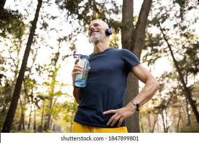 Low angle of smiling fit bearded male drinking water after running in earphones in park