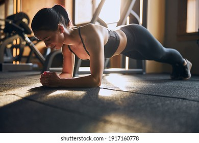 Low angle of smiling pretty female standing in plenk position on elbows while training in studio