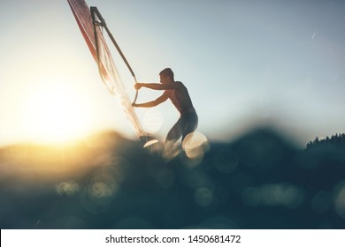 Low angle splashing view of windsurfer sailing on windsurf board. Windsurfer sailing on the surf board