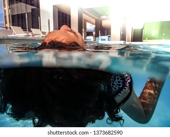 Low angle split view of girl's face above water and her hair and arm underwater, floating in an outdoor private swimming pool.