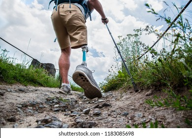 Low angle of a sporty disabled man with prosthesis walking along the path while leading a healthy way of life