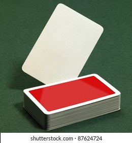 low angle studio photography showing a stack of red playing cards on green felt background