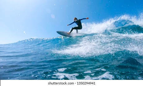 LOW ANGLE, SUN FLARE: Cool young surfer dude carves a beautiful blue tube wave near Fuerteventura. Athletic male tourist enjoying his summertime by surfboarding in the picturesque Canary Islands.