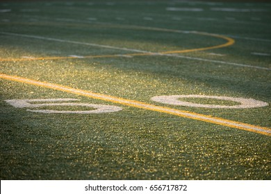 Low angle telephoto perspective of fifty yard line center field of professional or high school football artificial turf field painted with yellow and white stripe in dramatic game time sunset sunlight