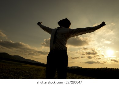 Low angle three quarter body view of silhouetted person with spread arms in countryside sunset, freedom concept.