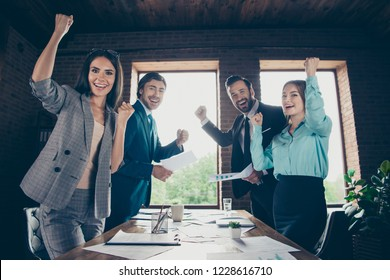 Low angle top view of four attractive person raised fists up people team after seminar training look at camera make hollywood smile stand inside loft interior workstation