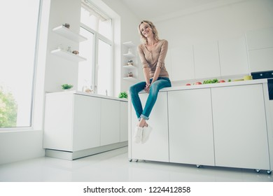 Low angle top view photo of romantic tender gentle lady with her soft white smile she look at camera sit on table in bright light house interior