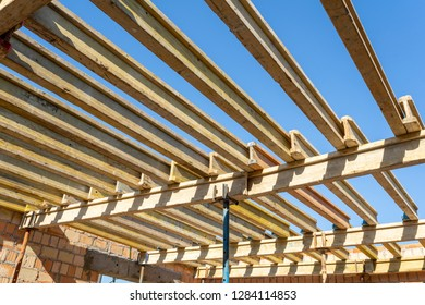 Low angle top view photo of formwork construction. Small unfinished building with wooden ceiling beam on support pipes under blue sky