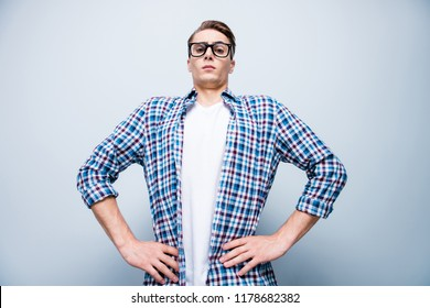 Low angle top view portrait of cpmic, handsome, attractive, sporty guy in blue checkered shirt and white t-shirt look at camera hold hands on waist isolated on light gray background