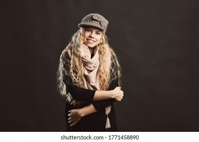Low angle of trendy pleased teenager in black jacket and gray knitted hat and beige scarf smiling at camera while standing with arms crossed against black background in studio