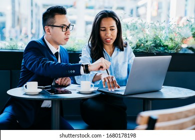 Low angle of troubled diverse colleagues in elegant clothes focusing on screen and trying to solve problem while sitting at table and interacting with laptop during coffee break in modern cafe