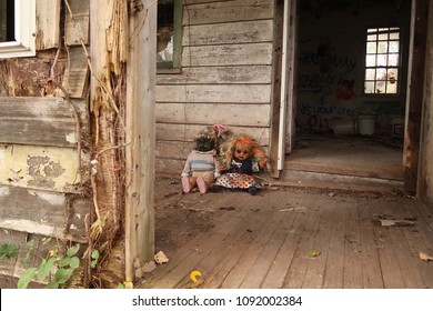 Low angle of two creepy dolls on the front porch of an abandoned house. Focus is on the dolls.