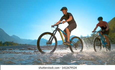 LOW ANGLE: Two guys riding ebikes along the shallow river and splashing refreshing water on a sunny day in beautiful Slovenian nature. Active young friends spraying water during a mountain bike ride.