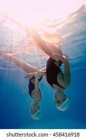 Low angle underwater view of synchronized swimming duet