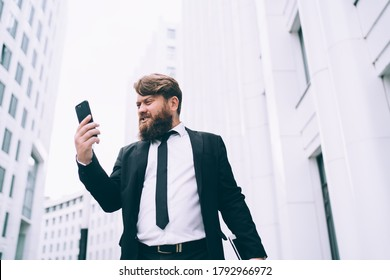Low angle of very angry male entrepreneur in smart suit standing in city street and looking at smartphone screen in displeasure