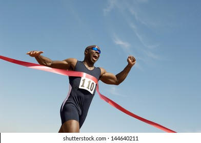 Low angle view of an African American male runner winning race against blue sky