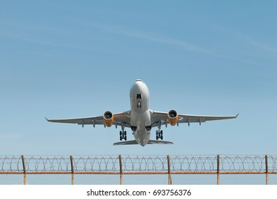 Low angle view of airplane flying over the fence.